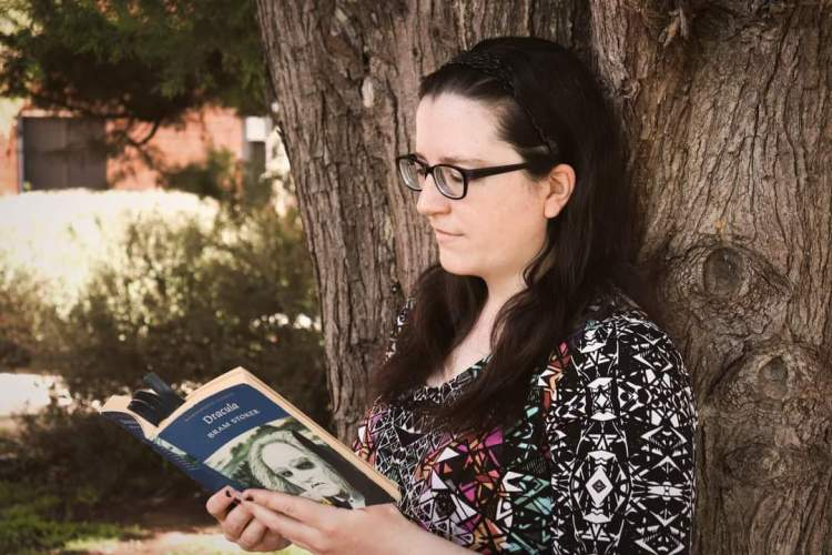 A woman wearing a colourful top, with long hair out and over her shoulders. She is leaning against a tree. She is reading a paperback copy of Dracula.