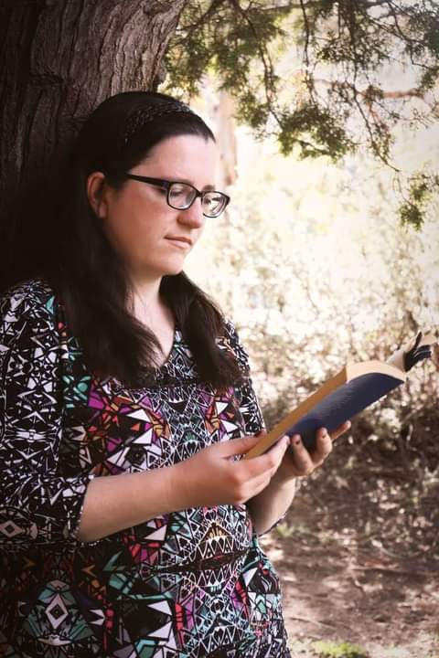 A woman wearing a colourful top, with long hair out and over her shoulders. She is leaning against a tree. She is reading a book with a blue cover.