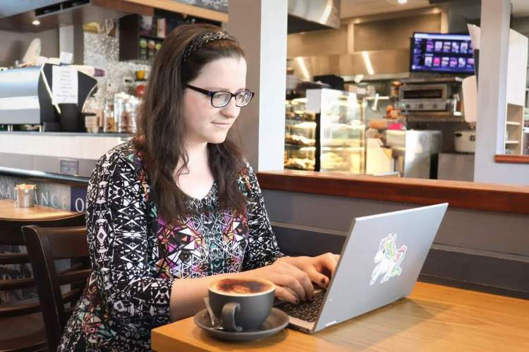 A woman wearing jeans and a colourful top, with long hair out and over her shoulders. She is sitting at a table at a cafe, looking at a laptop. There is a cup of coffee on the table beside the laptop.