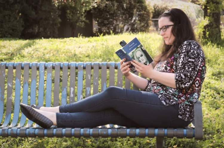 A woman wearing jeans and a colourful top, with long hair out and over her shoulders. She is sitting with her legs stretched along a park bench. She is reading.